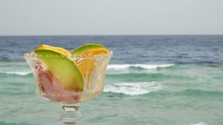 Ice cream balls with slices of orange and melon fruit on a background of blue and turquoise sea or ocean on a beach on a sunny day