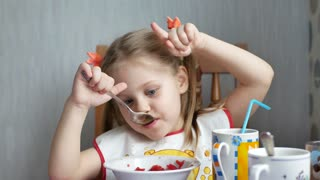 Little blue-eyed girl with blond hair is played and shows her fingers like a cow's horns in the kitchen of the house