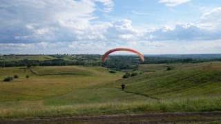 Man Paragliding. Glider Moves Smoothly Through The Air. Paragliders Flying An Extreme Sports Event On A Paraglider. Person Fly On Paraglider On Background Of Green Grass On Sunny Day