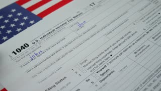 Man Person John Doe Is Writing Personal Information In The US Individual Income Tax Return Form 1040 in 2017 With American USA Flag