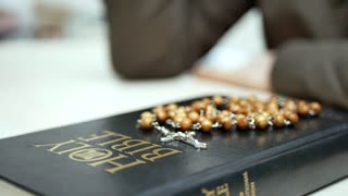 Sunday Bible reading in church. Holy bible on the table with wooden rosary with cross