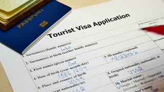 The decision to grant a visa. Pen voting denied in checkbox in blank Tourist Visa application form with passport and pen. Document with passport, apply and permission for foreigner country
