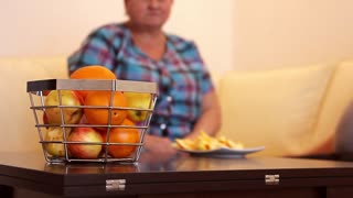 Adult woman sitting at home table eating fresh fruit.