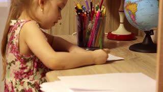 Beautiful little girl is drawing with pencils on paper in his room.