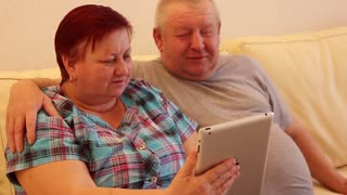 Beautiful old couple is using a digital tablet and smiling sitting on couch