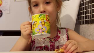 Cute little girl is having a breakfast. Child eating cookies and drinking tea.