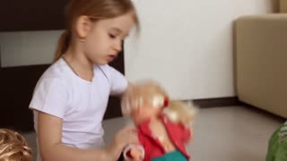 Cute little girl plays with doll's house