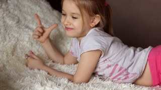 Cute little kid listening music lying on bed at home
