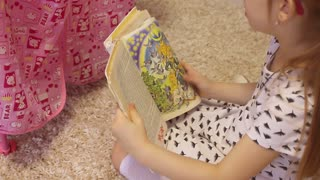 Cute toddler girl with blond curly hair reading a book sitting