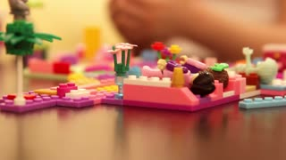 Girl child playing in Lego at the table