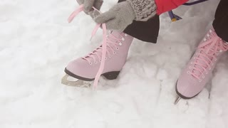 Girl in dress skates mittens tying shoelaces