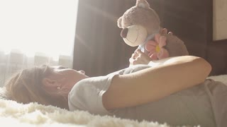 Girl is playing with a teddy bear and smiling while sitting on her bed at home