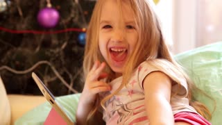Girl playing with tablet PC near Christmas tree