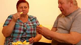 Happy elderly couple with fresh fruits.