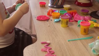 Kid girl playing with plasticine at home or kindergarten