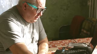 man in glasses working behind a laptop at home