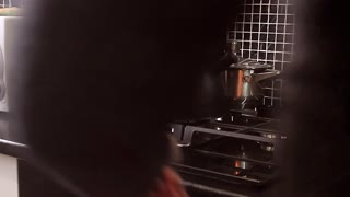 man in the kitchen to put the kettle on a gas stove.