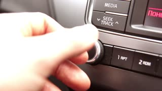 man using car audio and radio stereo on car panel
