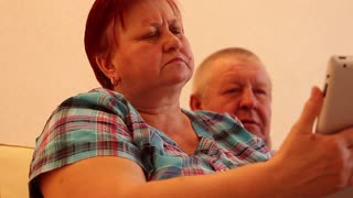 Mature couple using a tablet sitting on the couch