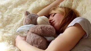 Sleeping girl with teddy bear in bedroom at home
