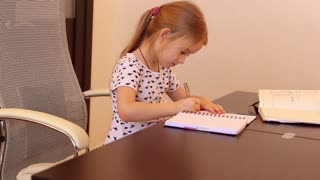 Smiling little office lady writing book on the desk