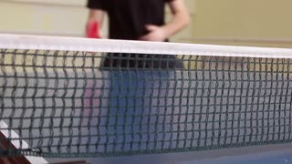 table tennis player returning ball, focus at the net.