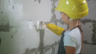 7 years old girl in a construction helmet painting the wall at a construction site
