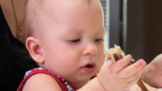 A baby boy is eating, sitting at a table, close-up.
