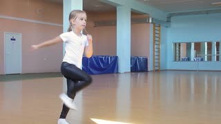 A beautiful girl is engaged in dancing in the dance hall. The child looks at the reflection and performs the exercises. Dancing school.