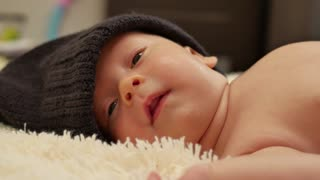 A charming little baby boy is looking into the camera and is wearing a black hat.