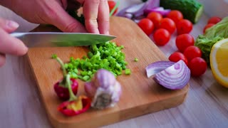 A chef chops green spring onions beautiful shot with soft focus. Healty food concept, vegetarian.
