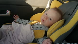 A cute little baby sits in a car seat, a smile and a joy of travel.