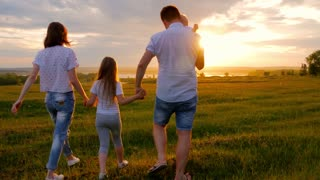A family with children is walking along the green meadow towards the sunset. Run, raising baby up in the air, hugs, love, playing. We are happy family.