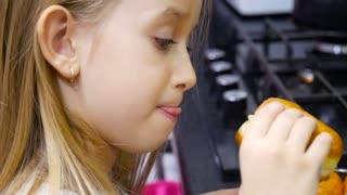 A girl eating a doughnut at a kitchen