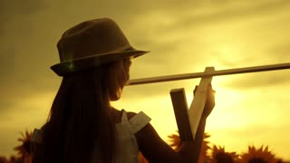A girl with hat playing with a wooden airplane. Happy child playing with toy airplane on sunflower field on sunset. In the rays of the sun, the rear view. Baby dream, childhood, memories concept.