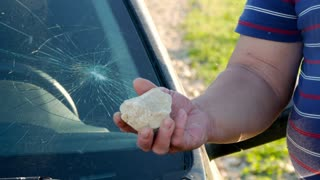 A hand holding a stone after breaking the glass of the car, vandalism.