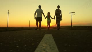 A happy family is walking along the road during sunset. The concept of a happy family, love and joy.