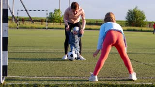 A happy mother with children playing soccer on a football field, score a goal, play in the air, lifestyle, the concept of the family.