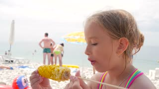 A little blond girl is eating corn on the beach.