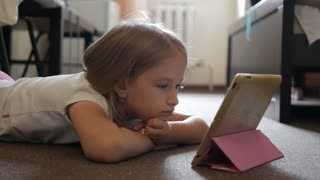 A little blond girl lying on floor at home and tapping on tablet while playing interesting game looking totally absorbed.