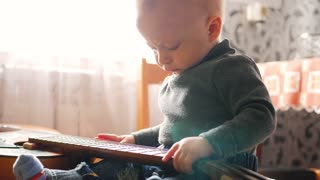 A little boy playing with a guitar at home.