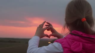 A little girl making heart symbol with her hands at sunset