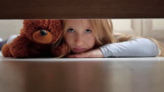 A little girl with her teddy bear looks under the bed. The concept of a child's dream.