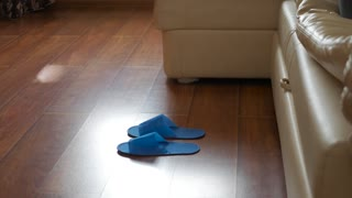 A man gets up at bed and wears disposable slippers at hotel.