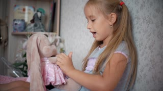 A small beautiful girl and a toy rabbit in the dress at home. Family relationships. The Child hugging lovely toy.