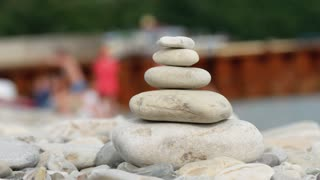 A stack of round stones standing on the shore of a sea. Concept of balance and harmony. Rocks on the coast of the Sea in the nature.