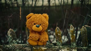 A teddy bear is sitting on a wooden fence.