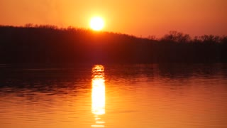 A time lapse of the large orange sunset as the massive sun sets into the horizon above the river