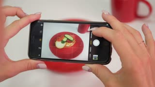 A woman in a restaurant takes a picture of food with a mobile phone camera. Take a photo of food in a restaurant with mobile phone camera for social network.
