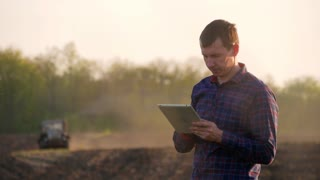 A young agronomist works in the field, uses a tablet. In the background, the tractor is out of focus. Farmer using digital tablet. Concept of technologies.